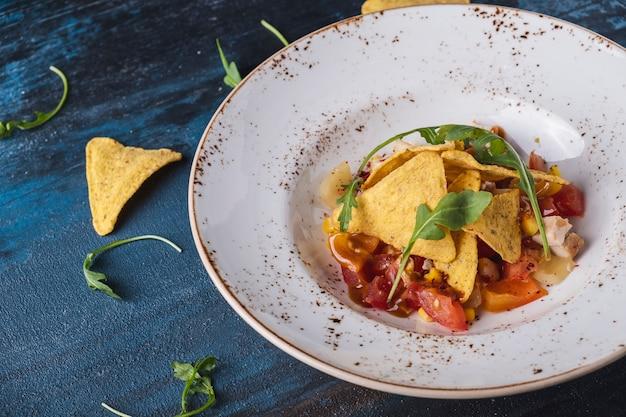 プレートにスモークチキンとコーンチップスを添えたおいしいメキシコ風サラダコピースペース