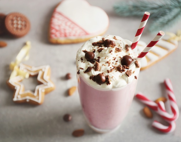 Delicious milkshake with christmas decoration on grey textured background