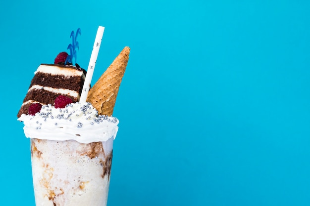 Delicious milkshake with ice cream cone and cake on blue background