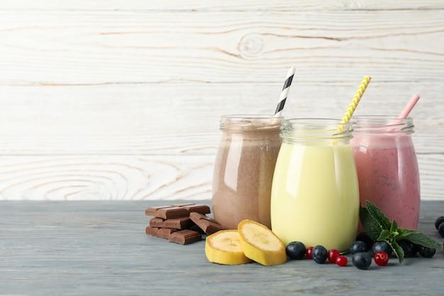 Вкусные молочные коктейли на деревянном фоне