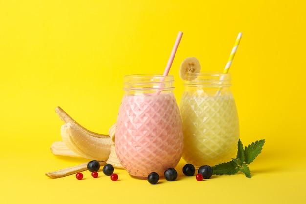 Вкусные молочные коктейли на желтом фоне. сладкий напиток