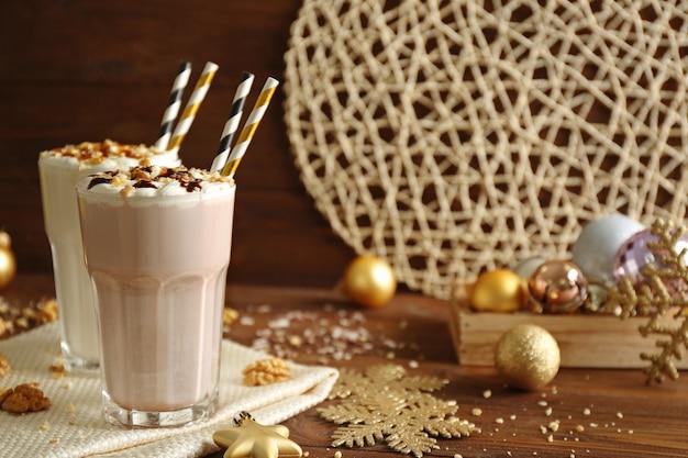 Вкусные молочные коктейли с рождественским украшением на деревянном столе крупным планом