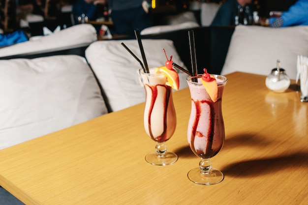 A delicious, milky, banana strawberry cocktail with an orange slice in large glasses on a table in a restaurant.