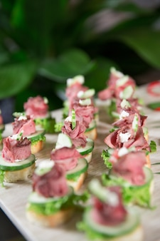 Delicious mini canapes with meat on buffet table