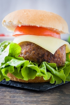 Delicious mini cheese burger with vegetables close up