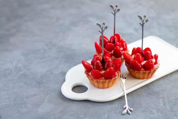 Delicious mini cheesecakes with fresh strawberries and cream cheese on light grey stone background