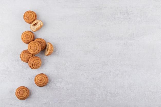 Вкусные мини-пирожные с корицей на каменном столе.