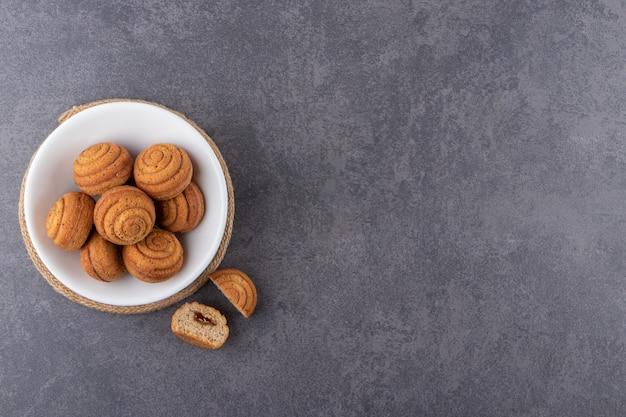 Deliziosi mini dolci alla cannella posti sul tavolo di pietra.