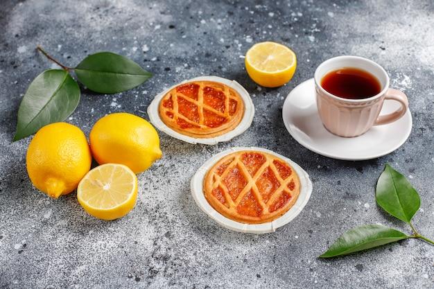 Delicious mini lemon pies with fresh lemons, top view