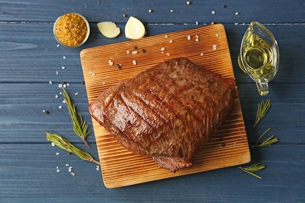 ボード上のおいしいしっとりステーキと青い木製のテーブル