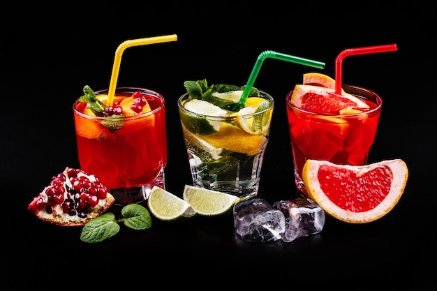 Delicious mojito, rum and cola, blood orange and vodka cocktails served with fruit