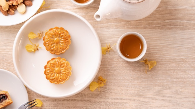 Delicious moon cake for mid-autumn festival with beautiful pattern, decorated with yellow flowers and tea