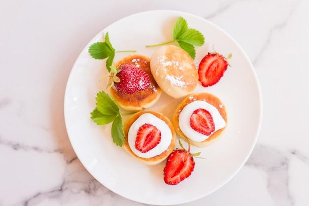 맛있는 아침 조식. 치즈 팬케이크. 딸기 조각과 사워 크림으로 아름답게 장식 된 두부 팬케이크.