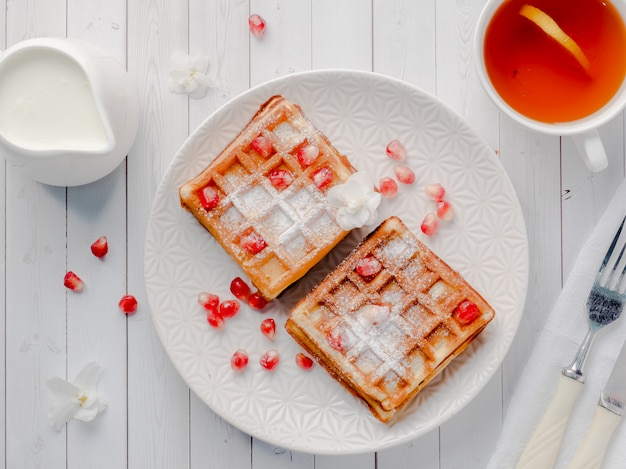 Delicious mouth-watering viennese waffles with honey and pomegranate seeds on a white plate