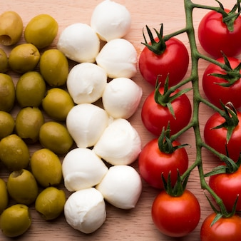 Delicious mozzarella cheese; fresh red tomatoes and wet olives on wooden table