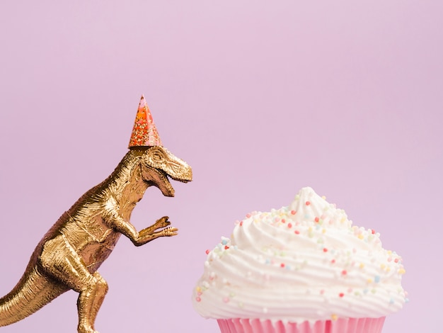 Delicious muffin and dinosaur with birthday hat