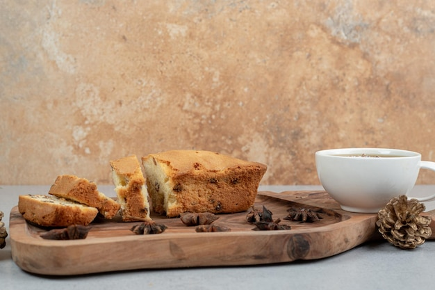 Delicious muffin with raisin and cup of tea on wooden board.