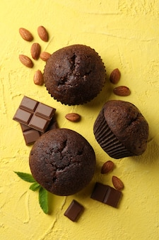 Delicious muffins, chocolate and almond on yellow background