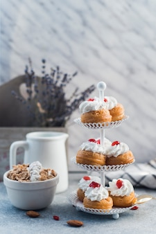 Delicious muffins on cake stand near bowl of cornflakes and almond on concrete surface