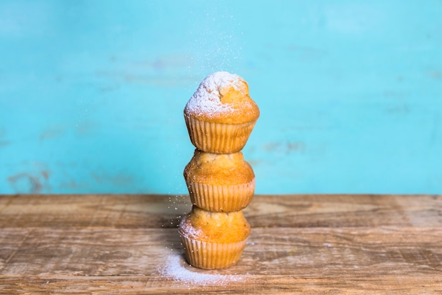 Delicious muffins tower on blue background