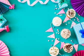Delicious muffins with party accessories on green surface