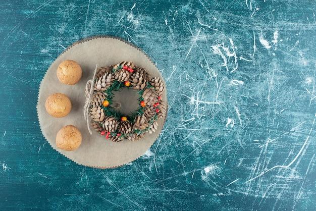 Deliziosi muffin con una corona di fiori su marmo.
