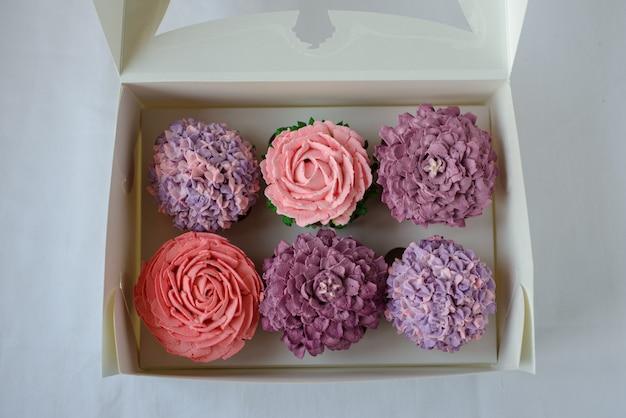 Вкусные разноцветные кексы в белой коробке.