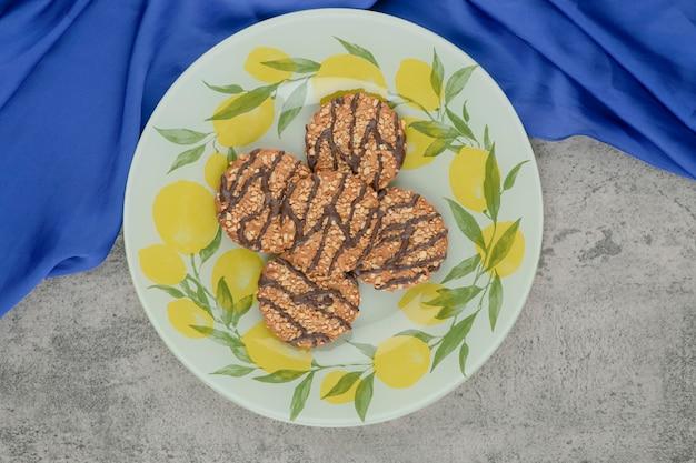 Вкусное печенье из мультизерна в шоколадной глазури на керамической тарелке.