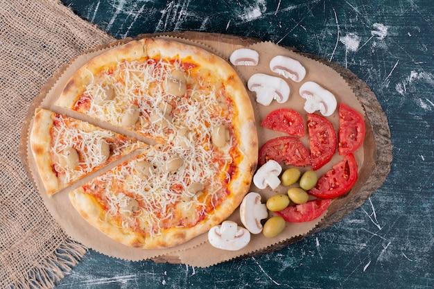 Deliziosa pizza ai funghi con formaggio e verdure fresche su marmo.