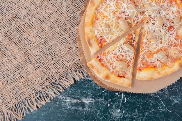 Deliziosa pizza ai funghi con formaggio su marmo.