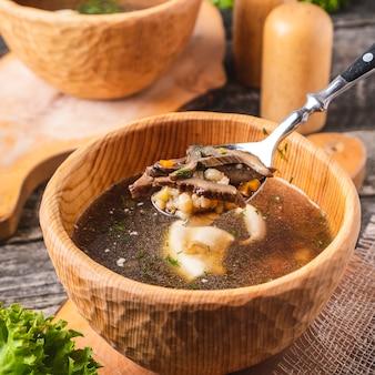Вкусный грибной суп в деревянной миске крупным планом