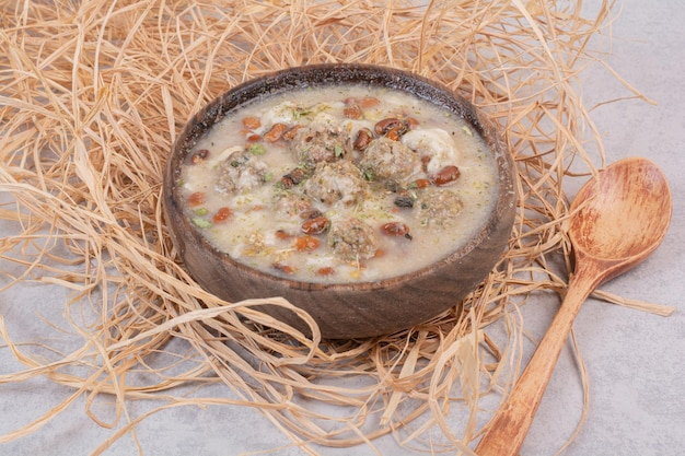 Вкусный суп из грибов в деревянной миске с ложкой.