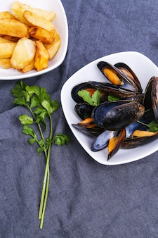 Delicious mussels on blue tablecloth