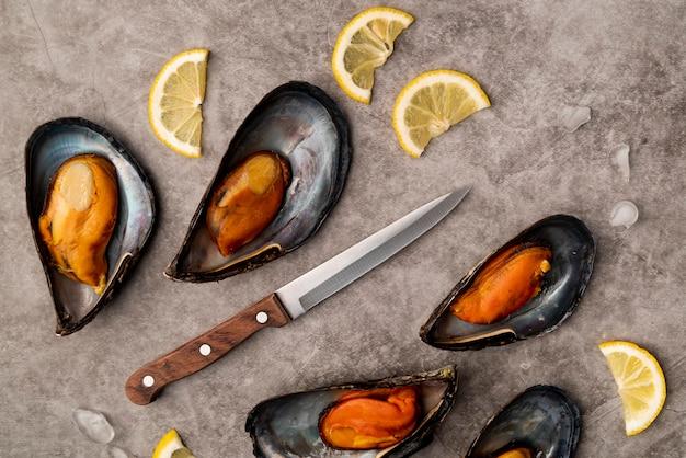Deliziose cozze e coltello distesi piatti
