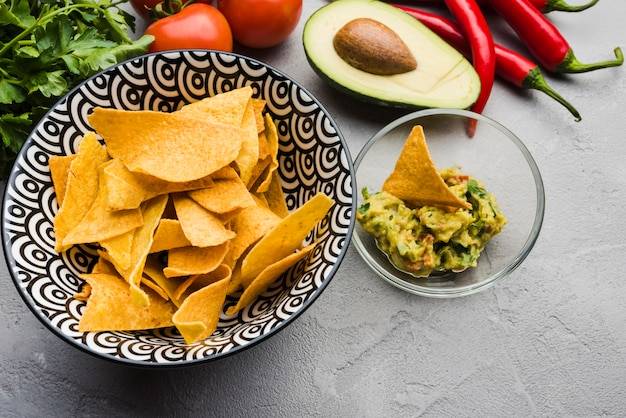 Delicious nachos near salad among vegetables and herbs