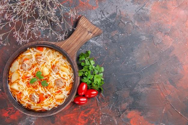 木製のまな板の上に鶏肉と暗いテーブルの上に緑のトマトの束とおいしいヌードルスープ