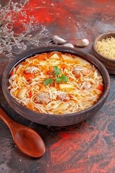 Deliziosa zuppa di noodle con pollo e pasta cruda in una piccola ciotola marrone e cucchiaio di aglio sullo sfondo scuro