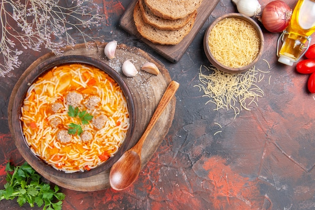 Delicious noodle soup with chicken on wooden cutting board greens spoon garlic onion and tomato on dark background
