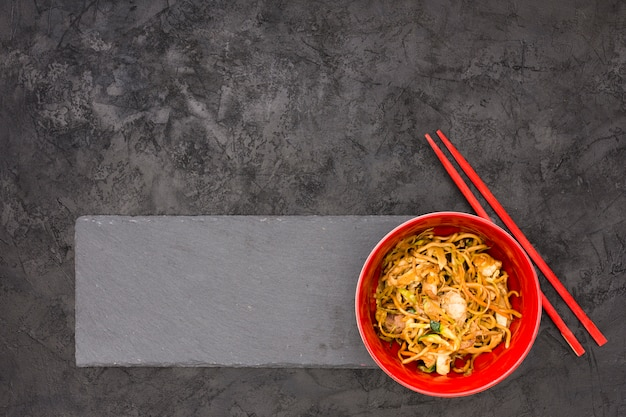 Delicious noodles on black slate with chopsticks over textured background
