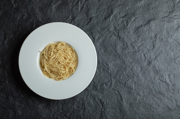 Delicious noodles in a white plate on black.