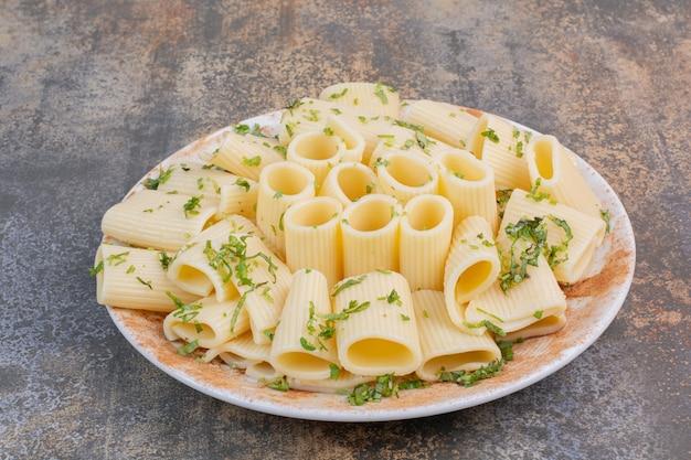 Вкусная лапша с зеленью на белой тарелке