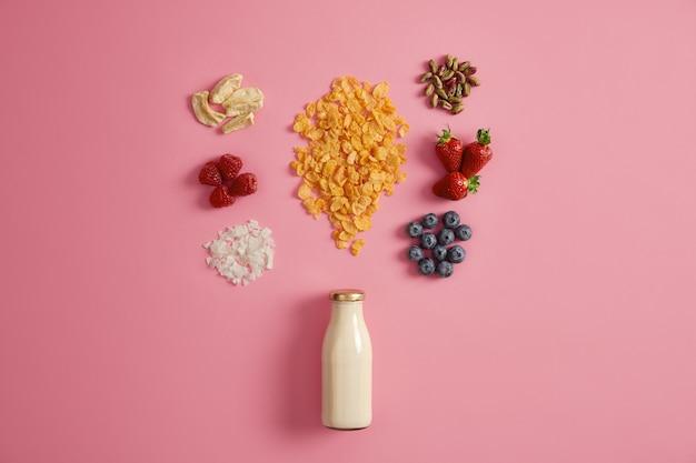 おいしい栄養のある朝食。グラノーラとおいしい材料を加えたミルクまたはヨーグルトのボトル。おいしい食事を準備するための乾燥リンゴ、ラズベリー、ココナッツフレーク、ピスタチオ、イチゴ、ブルーベリー