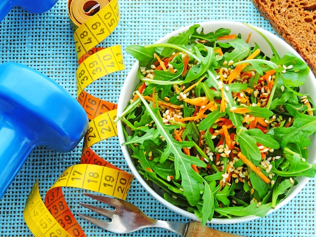 Delicious and nutritious fitness salad with arugula carrots and sesame. the concept of weight loss and sports lifestyle