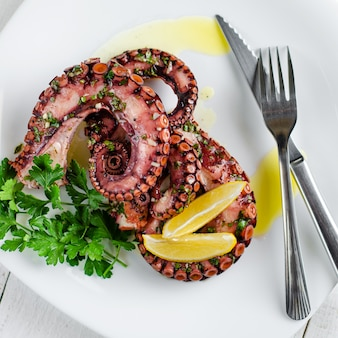 Delicious octopus salad with dressing, lemon and parsley on white background. healthy eating. seafood cooking