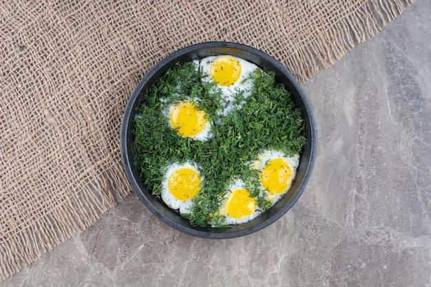 Вкусные омлеты с зеленью на темной сковороде на мешковине. фото высокого качества