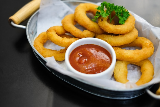 Delicious onion rings with tomato sauce serve on metal bowl