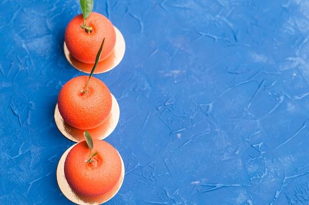 Вкусный апельсиновый торт в форме апельсина на синем