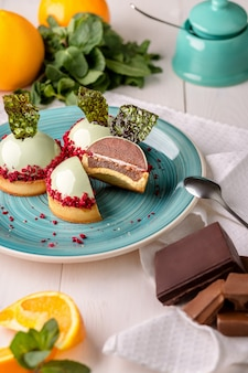 Delicious orange and chocolate cakes in the mirror mint glaze on a blue plate on a white wooden table in bakery