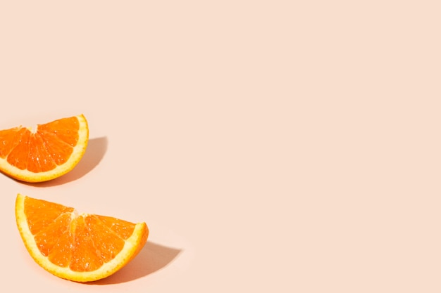 Delicious orange citrus fruit pieces on a light orange background