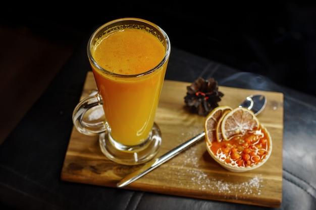 Вкусный апельсиновый коктейль с десертом и долькой апельсина на деревянной доске